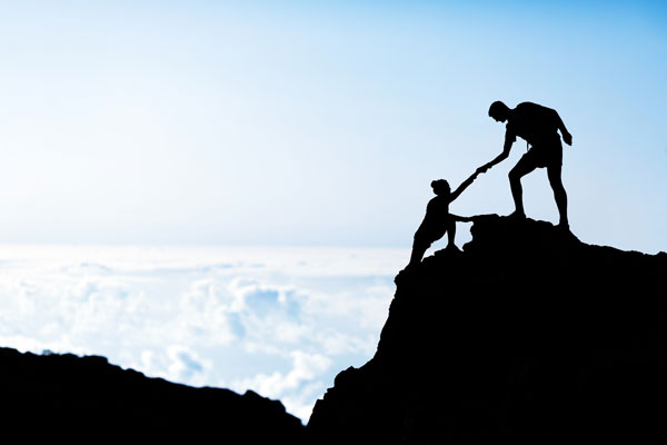 One climber helping the other similar to an Entrepreneur Coach